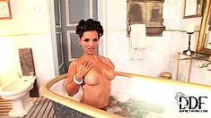 Sweet brunette poses, shows ass and gets all soaped up in the tub