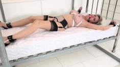 Mature blonde housewife with a generous rack wears a ball gag and is tied spreadeagled to the bed