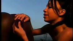 Ebony lesbians gently drill each other's tight holes with a big dildo by the pool