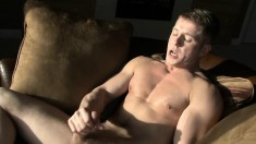 Tommy sits on the couch and pleases his throbbing pole with his hands