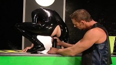 Kinky gay stud in a latex outfit has a big black toy exploring his ass